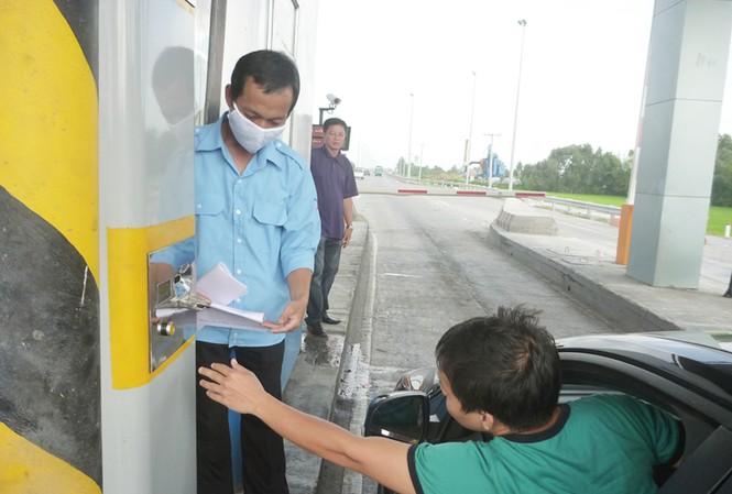 Lái xe bấm vào máy để nhận thẻ tại trạm thu phí Thân Cửu Nghĩa. Ảnh: Đức Thịnh
