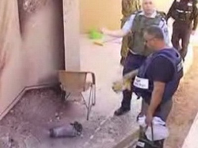 Cảnh sát Israel xem xét sân sau căn nhà bị pháo kích ở thành phố Sderot. Ảnh: Reuters