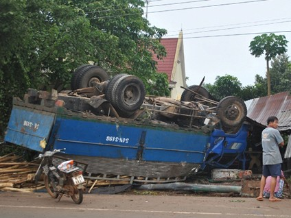 Nổ lốp, xe tải chở gỗ lật ngửa