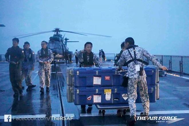 Thủy thủ trên tàu RSS Persistence của Singapore đưa thiết bị lặn tự động xuống nước để tìm máy bay QZ8501. Ảnh: Twitter