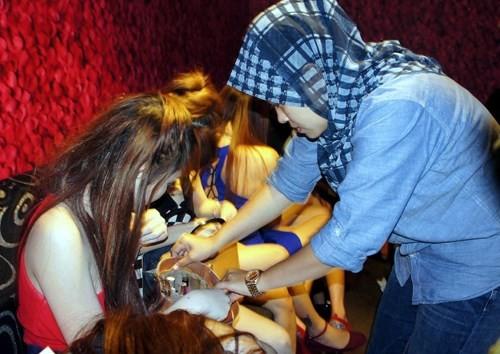 Cảnh sát thuộc Đơn vị Chống Buôn người thuộc cảnh sát Hoàng gia Malaysia kiểm tra hộ chiếu của một phụ nữ nghi là nạn nhân của nạn buôn người. (Ảnh: Bernama)
