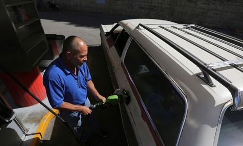 Henry Duran, một người dân Venezuela đang đổ đầy xăng cho chiếc Ford LTD Ranger sản xuất năm 1978 tại Caracas, Venezuela. Ảnh: AP