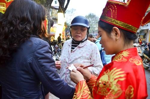 Nhân viên nhà hàng 'hóa trang' thần tài để giúp khách hàng viết phiếu, mua hàng. Ảnh: Thanh Hà