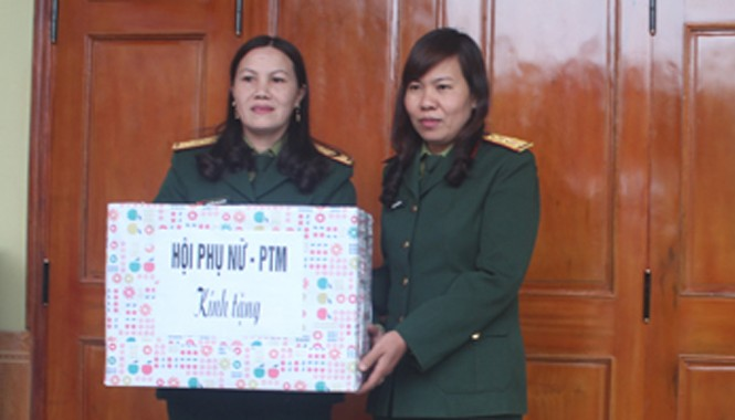 Đại diện Chi hội Phụ nữ Sư đoàn 324 tặng quà chị Sơn (trái) nhân dịp khánh thành nhà mới. Ảnh: Lê Tường Hiếu.