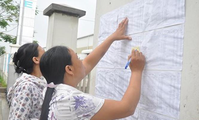 Công nhân ghi thông tin sổ BHXH trước cổng Cty TNHH Gmie (Bắc Ninh). Ảnh: T.T.