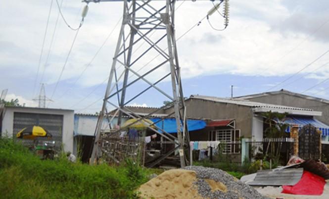Người dân làm nhà và sinh sống ngay dưới đường dây 220 kV vi phạm hành lang an toàn lưới điện cao thế nghiêm trọng. Ảnh: HL.