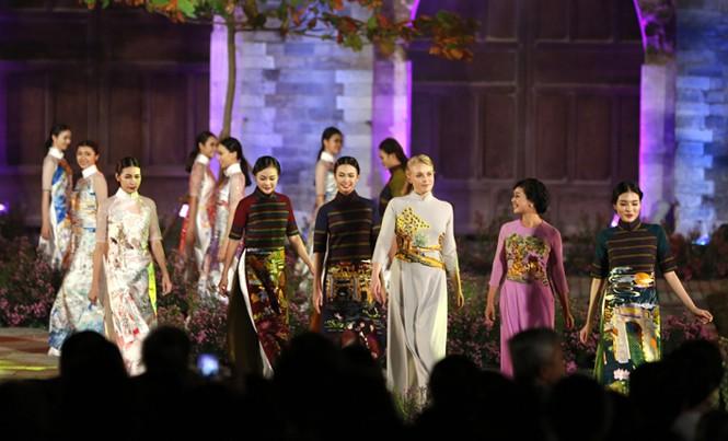 Nghệ sĩ, người mẫu và khách quốc tế trình diễn áo dài tại cổng thành Thăng Long. Ảnh: Hồng Vĩnh.