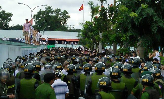 Các học viên leo lên tường, trong khi hàng trăm học viên khác đang đối đầu với công an tại trung tâm cai nghiện Đồng Nai ngày 6/11/2016. Ảnh: Anh Tuấn.