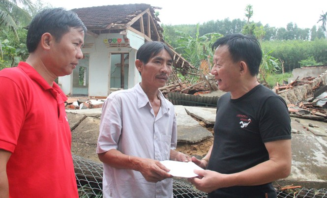 Ông Nguyễn Thanh Tú - Chánh văn phòng, Chủ tịch công đoàn Công ty Vinamilk trao tiền hỗ trợ cho gia đình bị thiệt hại do mưa lũ. Ảnh: Hoài Văn.