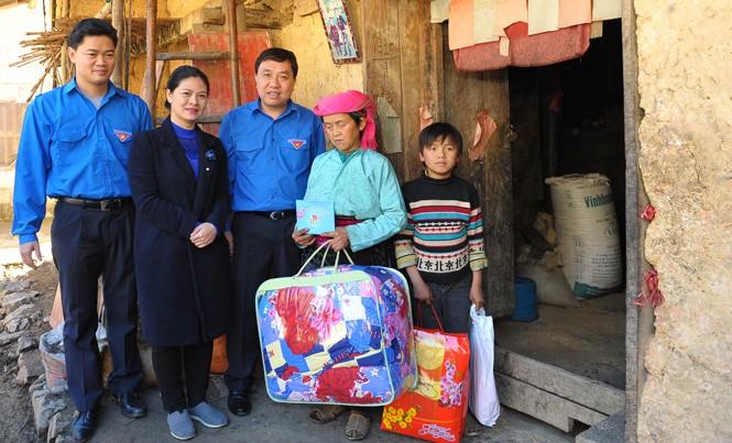 Bí thư thường trực T.Ư Đoàn Nguyễn Mạnh Dũng (giữa) tặng quà cho gia đình bà Vừ Mí Trứ. Ảnh: Xuân Tùng.