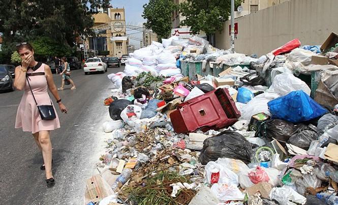 Một phụ nữ bịt mũi đi qua bãi rác thải tạm thời ở Jdeideh, phía đông bắc thủ đô Beirut của Li-băng. Ảnh: Getty Images.