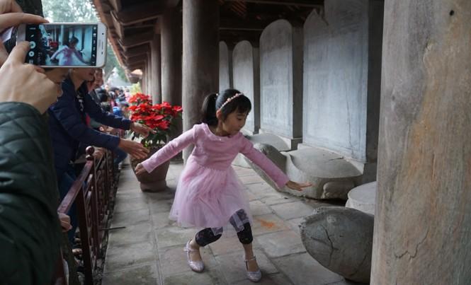 Một số phụ huynh vẫn xui con trẻ vượt rào vào sờ đầu rùa ở Văn Miếu. Ảnh: Nguyên Khánh.