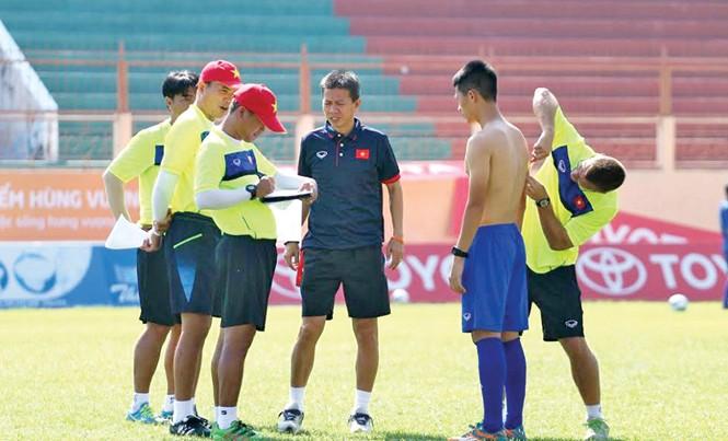 HLV Hoàng Anh Tuấn (giữa) cùng các cộng sự kiểm tra các chỉ số sinh học và thể lực của các cầu thủ. Ảnh: VSI.