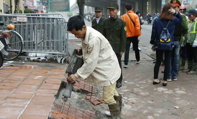Cơ quan chức năng đang tháo dỡ các công trình lấn chiếm hè đường Nguyễn Trãi, Hà Nội. Ảnh: Như Ý.
