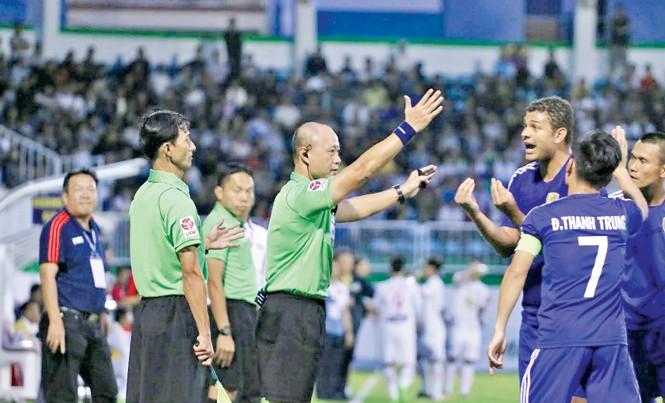 Trợ lý Phan Việt Thái (trái) và trọng tài Hoàng Anh Tuấn (giữa) bị cầu thủ Quảng Nam bao vây phản đối ở trận HAGL – Quảng Nam. Ảnh: Trần Khánh.