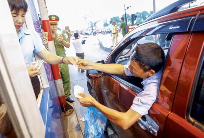 Tài xế trả tiền lẻ qua trạm thu phí BOT số 1 trên quốc lộ 5 (huyện Văn Lâm - Hưng Yên). Ảnh: Như  Ý.