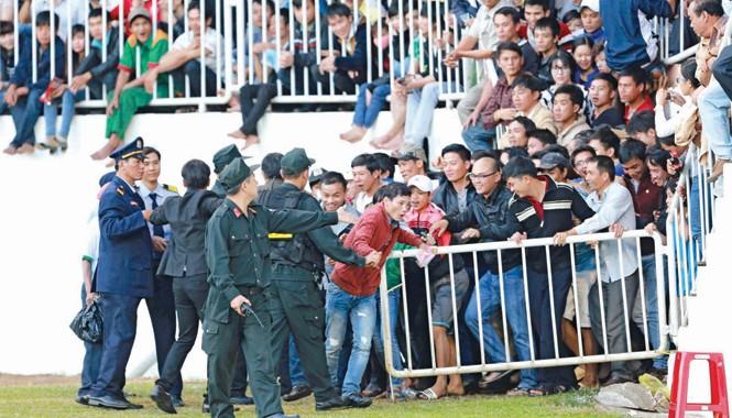 Lực lượng bảo vệ mở hàng rào cho khán giả tràn xuống đường piste sau khi lượng CĐV vào sân vượt sức chứa của sân Pleiku. Ảnh: VSI