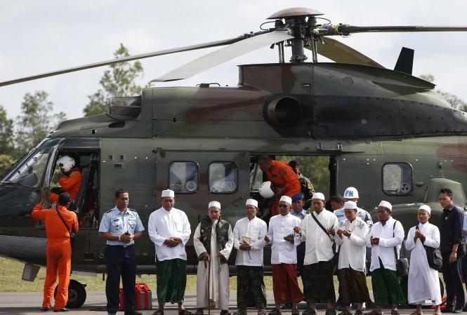 Các giáo sĩ Hồi giáo cầu nguyện trước khi lên trực thăng của quân đội Indonesia để tới hiện trường vụ máy bay rơi và cầu nguyện cho các nạn nhân - Ảnh: Reuters