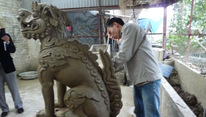 Nghệ sỹ Văn Vũ tạo tác mẫu bằng đất sét mô phỏng nghê Việt thế kỷ XVII ở đền vua Lê. Ảnh: Anh Phạm