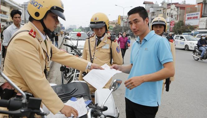 Tổ cơ động mạnh, CSGT Công an thành phố Hà Nội lập biên bản phạt lái xe taxi dừng đỗ sai. Ảnh: Hồng Vĩnh