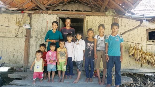 Vợ chồng A Thai-Y Đ'ưi và 9 đứa con (một đứa được gửi ở nhà ông bà ngoại) trước căn nhà rộng nhưng trống trơn. Ảnh: L.A
