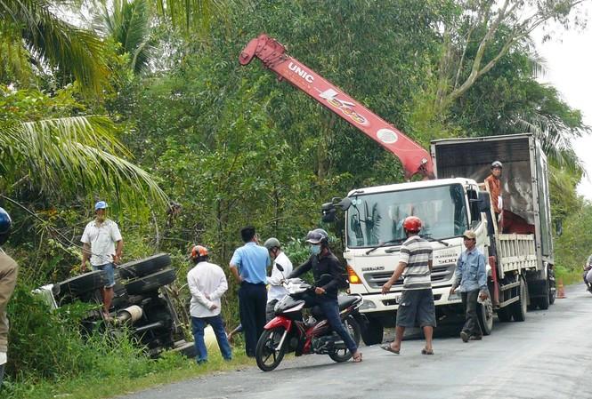 Chiếc xe tải nằm gọn dưới kênh và người dân phụ giúp chuyễn hàng lên bờ.