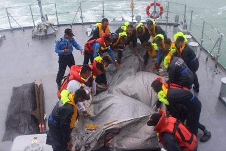 Các thành viên của đội cứu hộ trục vớt mảnh vỡ nghi là đuôi máy bay QZ8501