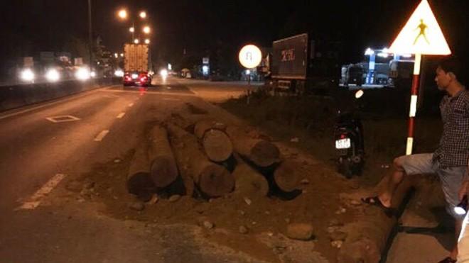 Sau khi đổ toàn bộ số gỗ trên xe xuống đường, gây cản trở giao thông, tài xế lái xe bỏ chạy.