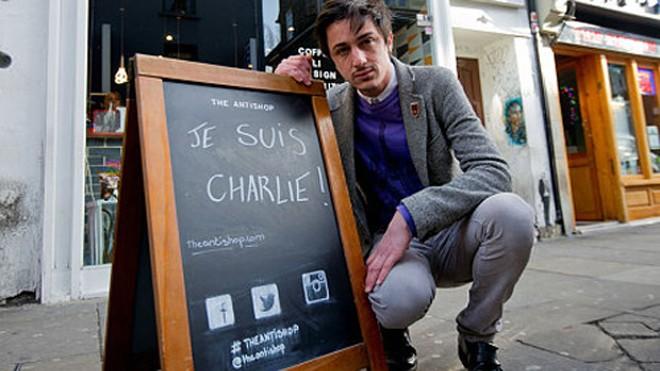 """Ông chủ Adel Defilaux bên tấm biển ghi """"Je Suis Charlie"""" đặt trước cửa quán cà phê của mình. Ảnh: Telegrpah."""