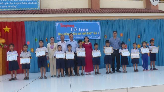 Các em học sinh nhận học bổng chụp hình chugn với baó Tiền Phong và Ban giám hiệu nhà trường.
