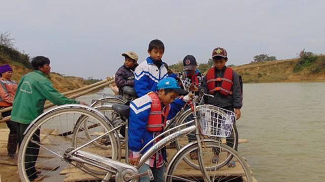 Học sinh Tiểu học luôn vất vả đưa xe lên thuyền mỗi khi qua sông. Ảnh: Đức Hùng