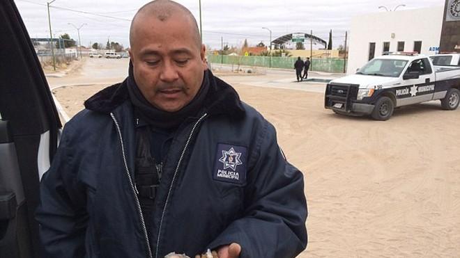 Thanh tra Umberto Mata nhặt những viên đạn trong cát ở thành phố San Agustin. Ảnh: Alasdair Baverstock