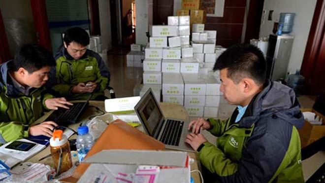 Deng cùng các cộng sự đang kiểm tra đơn hàng. Ảnh: People's Daily Online.