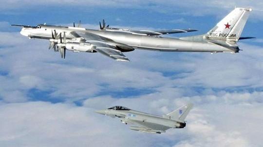 Một chiếc Tu-95 Bear (phía trên) được chiến đấu cơ Typhoon hộ tống ra khỏi không phận Anh tháng 4-2014. Ảnh: UK Mod