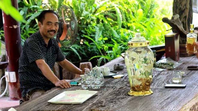 Anh Tuyền ngồi ngắm bình rượu sâm trên chiếc bàn gỗ hóa thạch khổng lồ, giữa khu vườn đầy hoa lá, chim muông