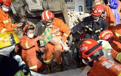 Lính cứu hỏa bế cô bé 3 tuổi ra khỏi ngôi nhà sập ở thành phố Ôn Châu. Ảnh: AFP