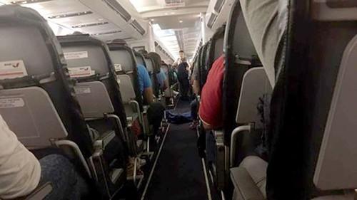 Thi thể nữ hành khách được phủ chăn và đặt ở lối đi giữa hai hàng ghế trên chuyến bay. Ảnh: CEN