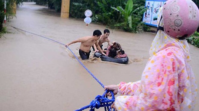 Các thanh niên địa phương hỗ trợ đưa cô và trò Trường Mẫu giáo An Hiệp (thôn Mỹ Phú 2) ra khỏi nơi bị ngập.