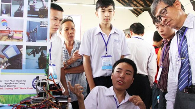 Trần Phan Thanh Hải đang giới thiệu mô hình robot hỗ trợ người bị bại liệt. Ảnh: Mạnh Tùng