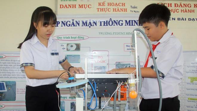 Khánh và Dung lắp đặt thử nghiệm hệ thống đập ngăn mặn thông minh sử dụng năng lượng mặt trời.
