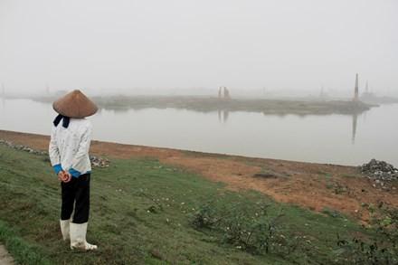 Một phụ nữ đứng trên đoạn đê mới được kè đá do bị sạt lở trên địa bàn xã Quế Tân (Quế Võ, Bắc Ninh). Ảnh: Trường Phong