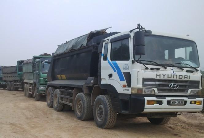 Hàng chục xe tải nối đuôi chở đất đi bán.