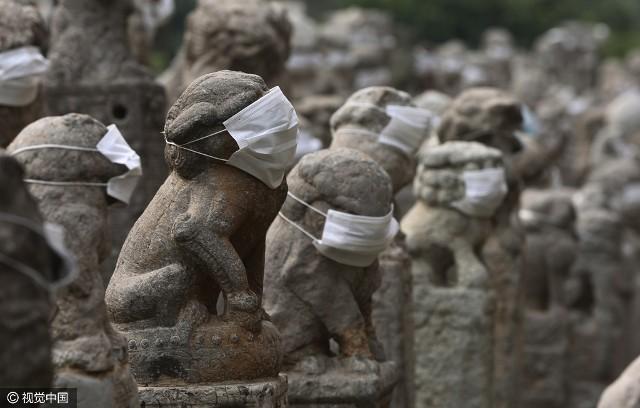 Không khí ô nhiễm, sư tử đá Trung Quốc được... đeo khẩu trang