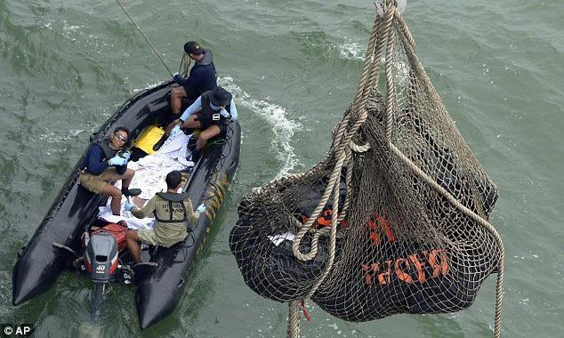 Các túi đựng thi thể hành khách chuyến bay QZ8501 được đưa từ thuyền nhỏ lên tàu hải quân Indonesia KRI Banda Aceh.