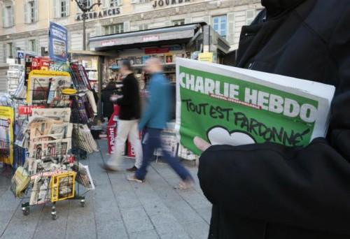 Một người cầm số mới nhất của tạp chí Charlie Hebdo. Ảnh: Reuters