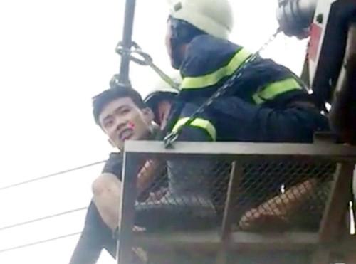 Thành được cảnh sát đưa xuống bằng xe thang.