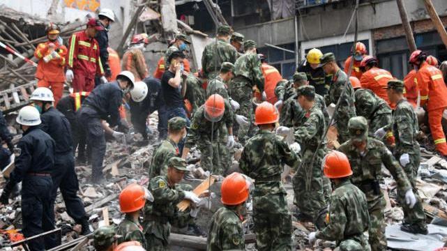 Các nhân viên cứu hộ dùng tay bới đống đổ nát cứu người mắc kẹt trong vụ sập nhà ở Ôn Châu, Trung Quốc.