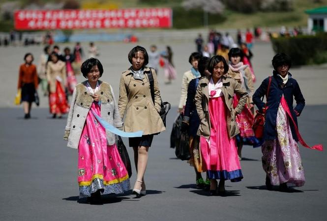 Phụ nữ Triều Tiên bước đi trên phố ở Bình Nhưỡng, Triều Tiên dịp nước này kỉ niệm 105 ngày sinh cố lãnh tụ Kim Nhật Thành. Cuộc sống người dân ở Bình Nhưỡng không có gì xáo trộn giữa lúc căng thẳng tăng cao trên bán đảo Triều Tiên sau khi Mỹ đưa cụm tàu s