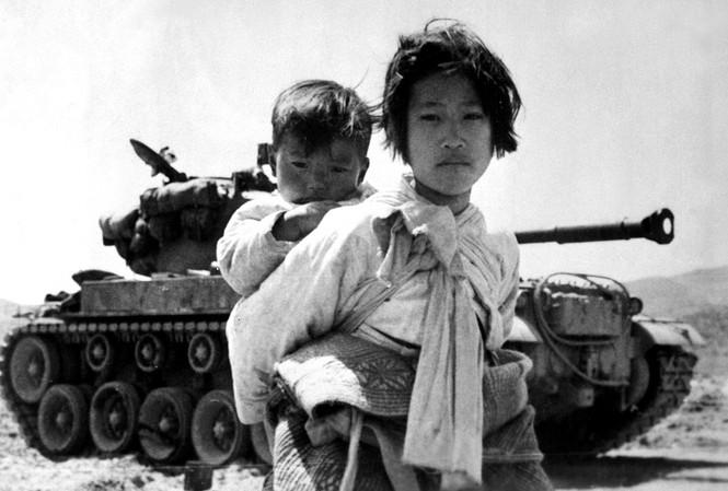Bé gái Triều Tiên cõng em đi qua một chiếc xe tăng M-26 tại Haengju, Hàn Quốc, ngày 9/6/1951.