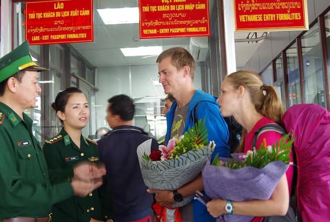 Đại diện Đồn Biên phòng Cửa khẩu Quốc tế Lao Bảo tặng hoa cho hai vị khách quốc tế đầu tiên nhập cảnh bằng thị thực điện tử qua đường bộ.